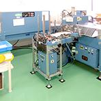 短納期や大量注文に対応するため、当社では専用の自動機を多数導入しています。(写真はシュリンク加工機)